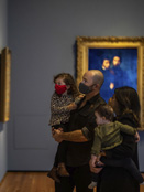 Family of four in gallery viewing artwork