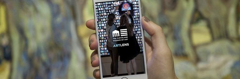 [image: a hand holding in iPhone, showing the opening screen of the ArtLens App]