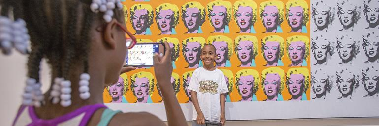 "A child taking a picture of another child in front of Andy Warhol's ""Marilyn x 100"" painting"
